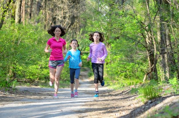 Sport per famiglie, madre attiva felice e bambini che pareggiano all'aperto, correndo nella foresta