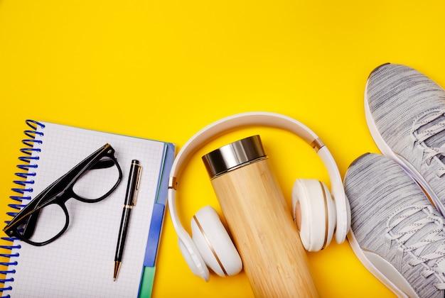 Sport piatto disteso con notebook, scarpe da ginnastica, auricolari e bottiglia d'acqua su sfondo giallo