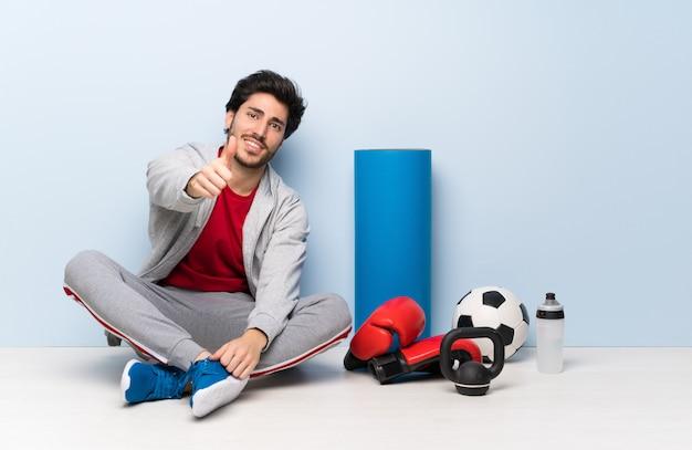 Sport uomo seduto sul pavimento con il pollice in alto perché è successo qualcosa di buono