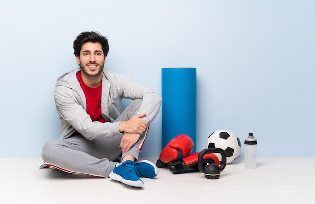 Sport uomo seduto sul pavimento mantenendo le braccia incrociate in posizione frontale