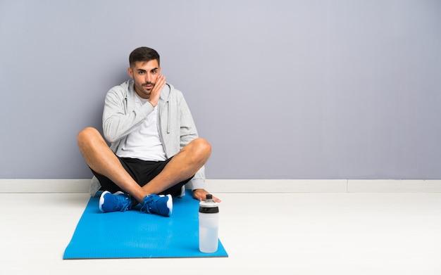 Sport uomo seduto uno sul pavimento sussurrando qualcosa