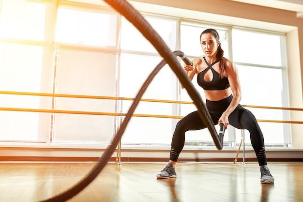 Sportiva che risolve con le corde di battaglia alla palestra