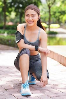 Sportiva etnica sorridente sul passaggio pedonale