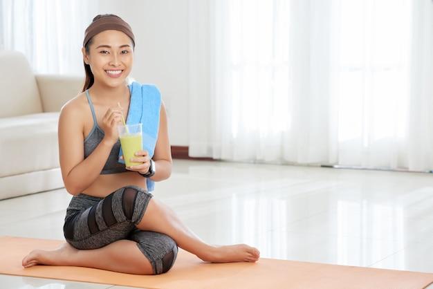 Sportiva sorridente con un bicchiere di frullato