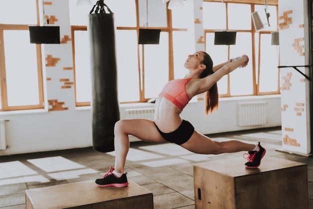 Sportiva sportiva sta esercitando in palestra da solo