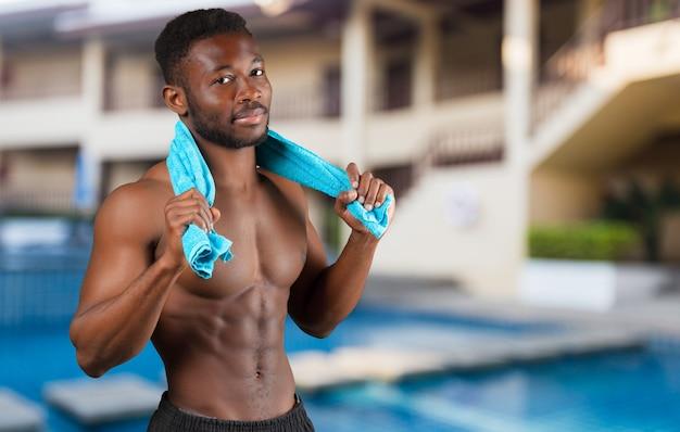 Sportivo africano bello allegro con l'ente forte muscolare che sorride alla macchina fotografica