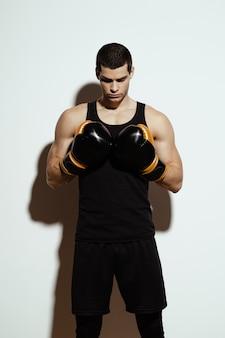 Sportivo attraente alto che posa in guantoni da pugile