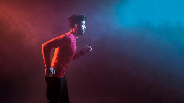 Sportivo che corre in fumo scuro
