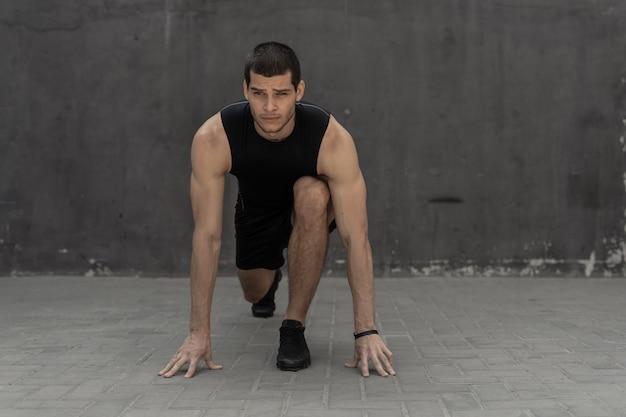 Sportivo che inizia il suo sprint su una parete industriale grigia
