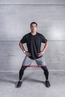 Sportivo che si esercita con elastico sulle gambe