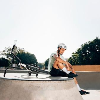 Sportivo che si siede nel campo lungo dello skatepark