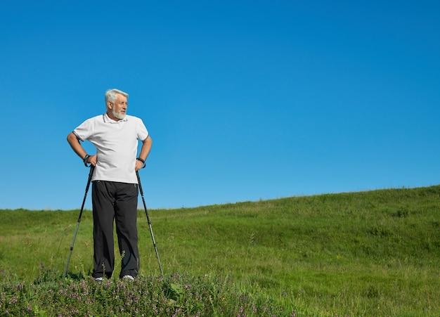 Sportivo che sta con i bastoni di inseguimento sulla collina verde.