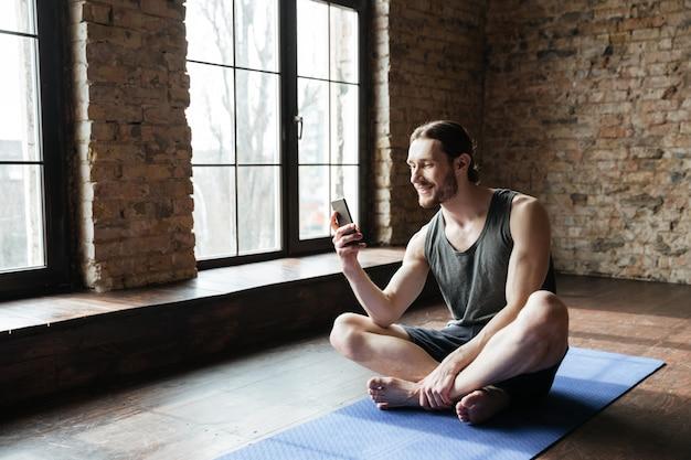 Sportivo concentrato sorridente che per mezzo del telefono cellulare