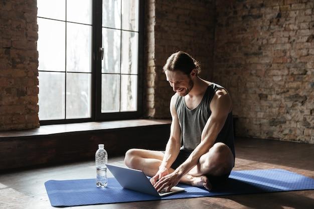 Sportivo forte bello che si siede vicino alla bottiglia di acqua facendo uso del computer portatile