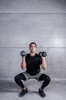 Sportivo moderno facendo squat con manubri