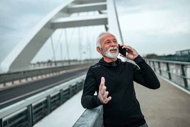 Sportivo senior che parla sul telefono all'aperto nella città.