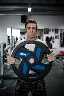 Sportivo serio che si esercita con il peso
