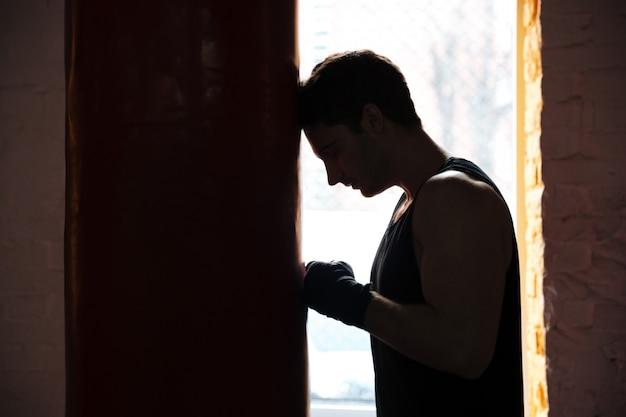 Sportivo stanco dell'uomo che si appoggia punchbag durante l'allenamento