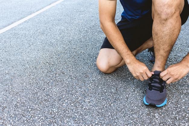 Sportman del primo piano che lega le scarpe da corsa