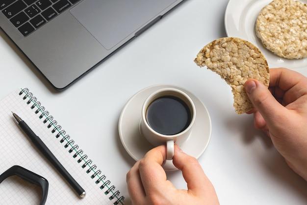 Sportsman che mangia i tondi croccanti del riso con caffè vicino al computer portatile ed al taccuino.