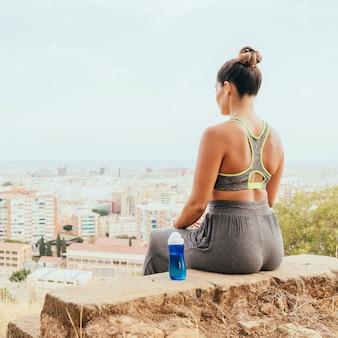 Sportswoman, bottiglia d'acqua e la città