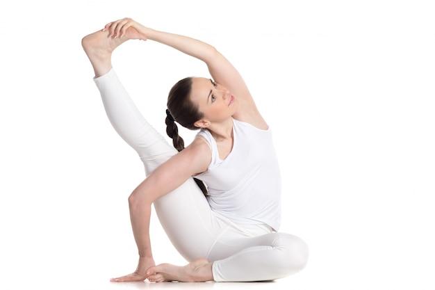 Sportswoman che si siede sul pavimento che si estende la gamba destra