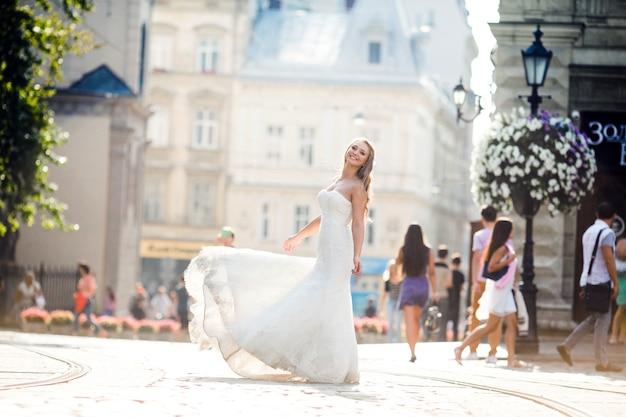 Sposa affascinante in abito splendido sulla strada