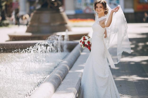 Sposa allegra tenendo il velo con la mano sinistra