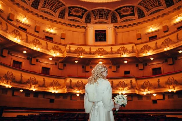 Sposa aspettare uno sposo in una vecchia sala del teatro