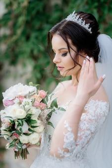 Sposa attraente in corona con bellissimo bouquet da sposa fatto di eustomas bianchi e rose rosa