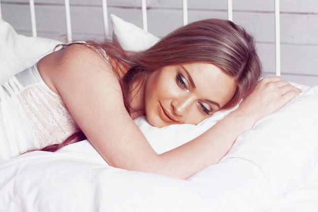 Sposa bella bella donna con un corpo sexy che giace in biancheria intima sul letto bianco