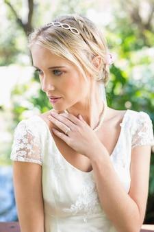 Sposa bionda contenta con la mano sul petto