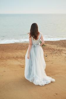 Sposa che cammina lungo la costa del mare indossando abito da sposa bellissimo