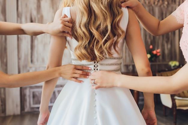 Sposa che mette sul suo vestito da sposa bianco. concetto di celebrazione del matrimonio. bellissimo abito da sposa in pizzo della sposa con schiena aperta.