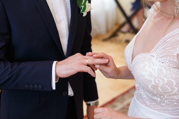Sposa che mette un anello sul dito dello sposo durante la cerimonia di nozze