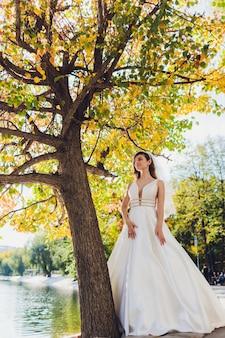 Sposa che posa in una ragazza verde del parco in un vestito bianco su un fondo di verde.