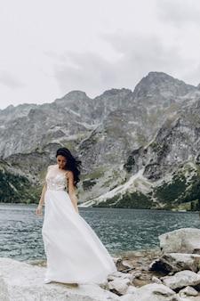 Sposa che sta sulla riva pietrosa del lago sea eye in polonia. vista panoramica sulle montagne. morskie oko. monti tatra.
