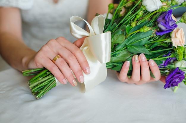 Sposa che tiene il bello mazzo di nozze nel giorno delle nozze