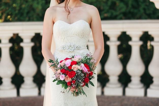 Sposa che tiene il grande mazzo di nozze su cerimonia di nozze con le colonne nel fondo