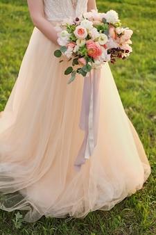 Sposa che tiene un mazzo di nozze nei colori di rosa pastello.