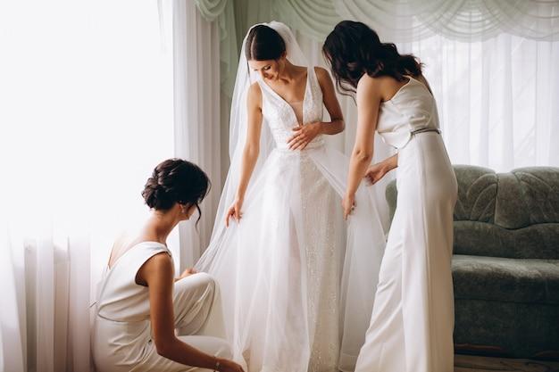 Sposa con damigelle preparando per il matrimonio