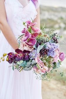 Sposa con i capelli rosa e un lungo abito da sposa in possesso di un bellissimo mazzo di fiori
