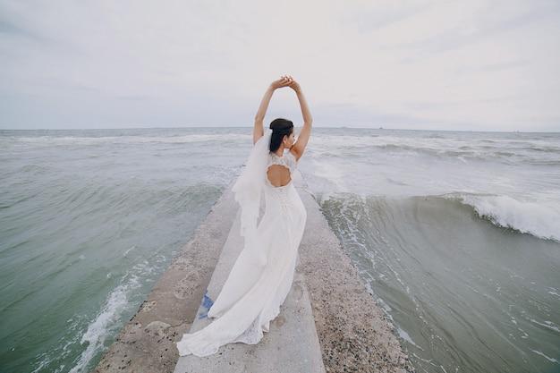 Sposa con le braccia alzate in mare