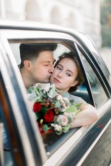 Sposa con lo sposo che si siede in vecchia retro automobile nera. newlyweds che baciano e che abbracciano mentre sedendosi dentro la vecchia retro automobile nera nel vecchio centro urbano. leopoli, ucraina