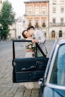 Sposa con lo sposo vicino alla vecchia automobile. sposi baci e abbracci mentre in piedi dietro la vecchia auto retrò nera nel centro storico della città. leopoli, ucraina