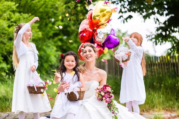 Sposa con ragazze come damigelle d'onore, fiori e palloncini