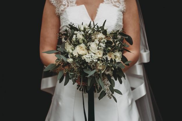 Sposa con un abito da sposa bianco che tiene un bellissimo bouquet di fiori sul nero