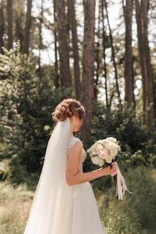 Sposa con un bouquet nel parco, abito bianco e velo