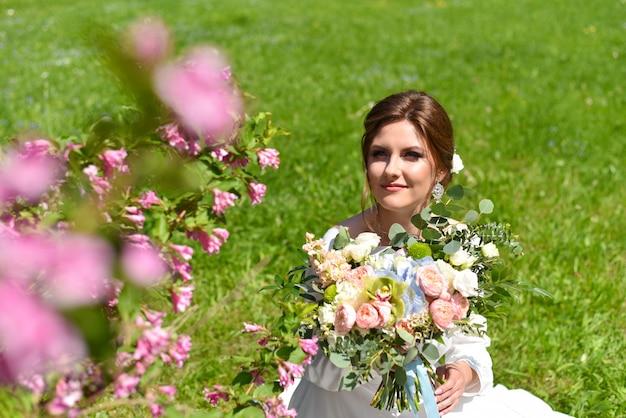 Sposa con un mazzo di fiori nel parco estivo