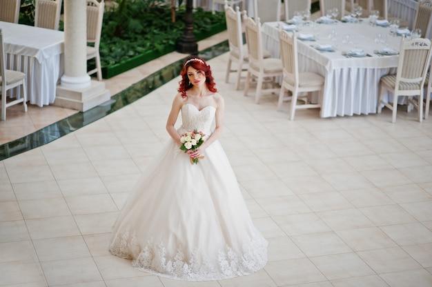 Sposa dai capelli rossi affascinante con il mazzo di nozze